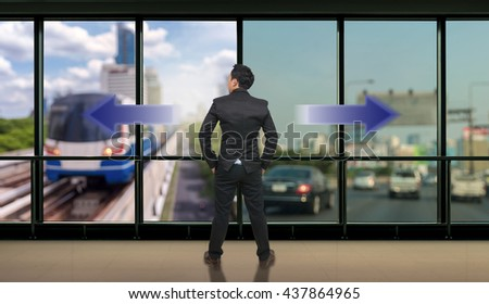 Businessman standing in doubt,thinking the two different choices of transportation for traffic jam with rush hour which indicated by arrows pointing in opposite direction, business decision concept