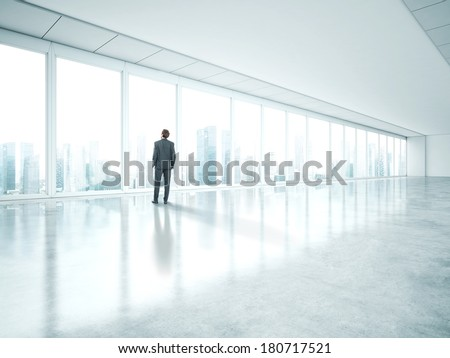 Businessman standing in empty bright office and look at city - stock photo