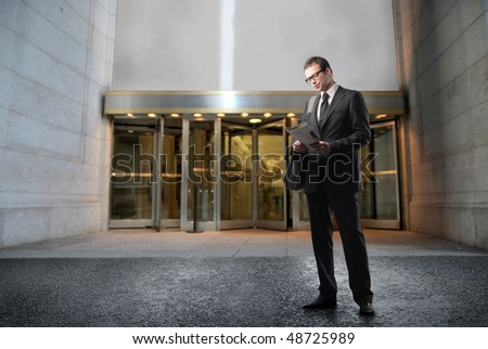 Businessman standing in front of a building - stock photo