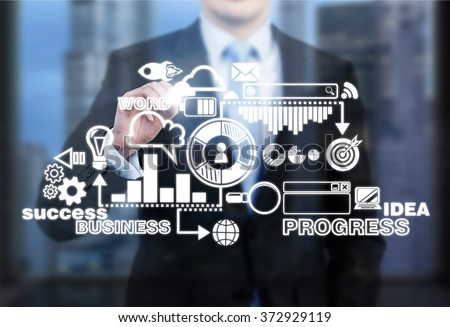 businessman standing in front of a business scheme touching it with fingers. Front view, no head seen. Blurred city view at the background. Concept of devloping a business. - stock photo