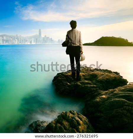 Businessman standing in front of a coastline and observing a cityscape on the background