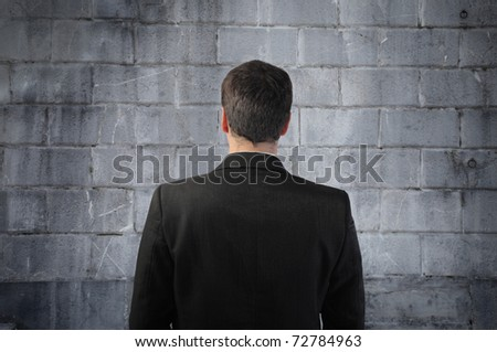 Businessman standing in front of a wall - stock photo