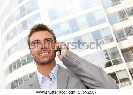 Businessman standing in front of building with telephone