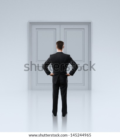 businessman standing in front of closed doors