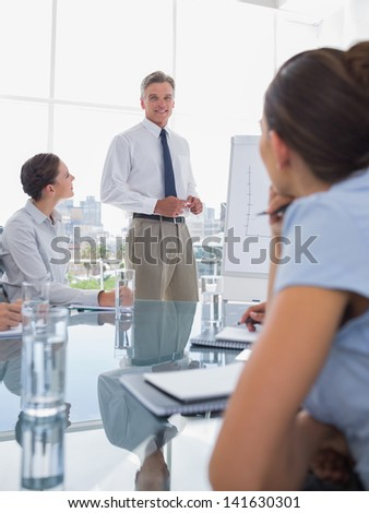 Businessman standing in front of colleagues during a meeting - stock photo