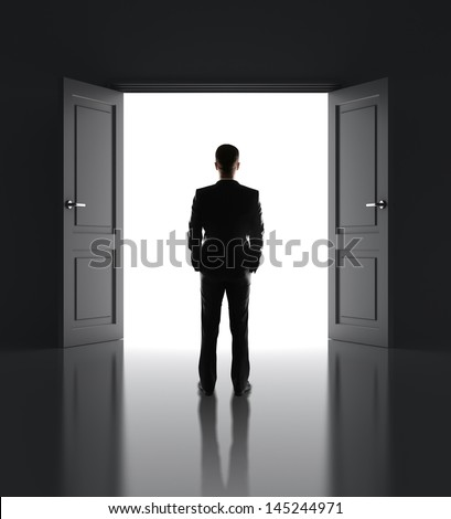 businessman standing in front of opened doors - stock photo