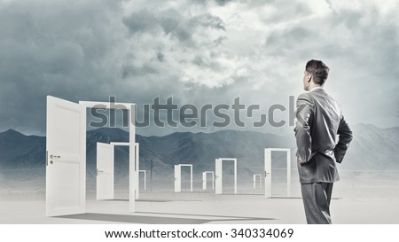 Businessman standing in front of opened doors and making decision - stock photo