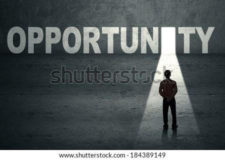 Businessman standing in front of opportunity door - stock photo