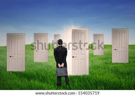 Businessman standing in front of opportunity doors at field - stock photo