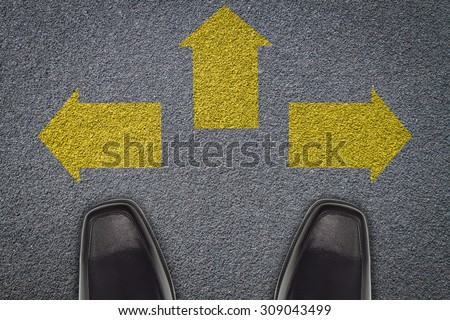 businessman  standing in front of three arrows  on asphalt road, business concept to success. - stock photo