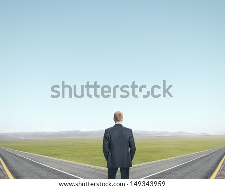 businessman standing in front of two roads - stock photo
