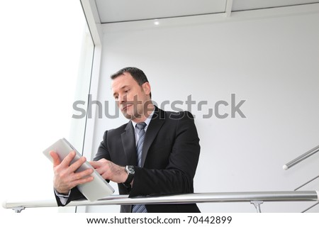 Businessman standing in hall with electronic tablet - stock photo