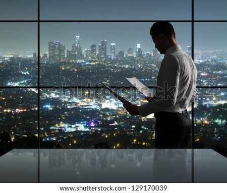 businessman standing in night office - stock photo