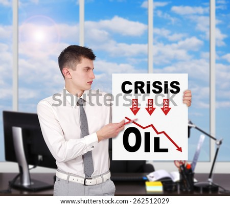 businessman standing in office and holding placard with crisis concept