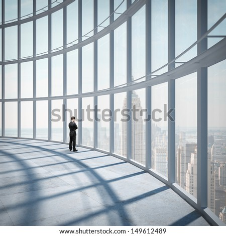 businessman standing in office and looking at city in window - stock photo