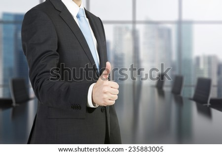 businessman standing in office and showing thumb up