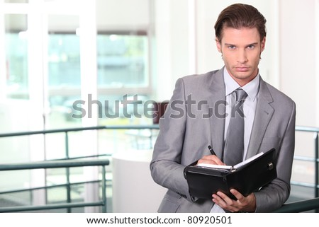 Businessman standing in office holding diary - stock photo