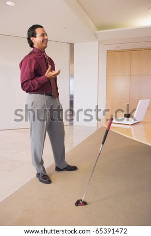 Businessman standing in office with golf club