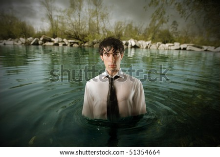 Businessman standing in the middle of water - stock photo