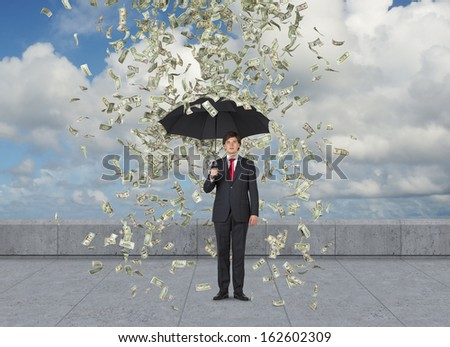 Businessman standing in the rain of dollars over sky background
