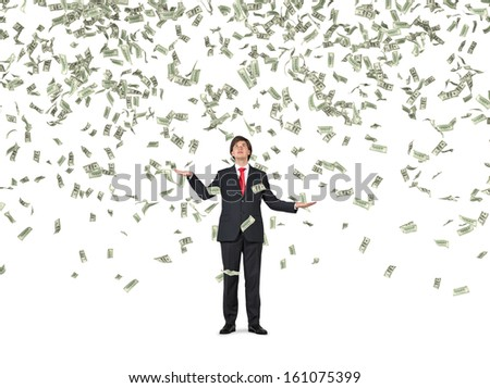 Businessman standing in the rain of money.