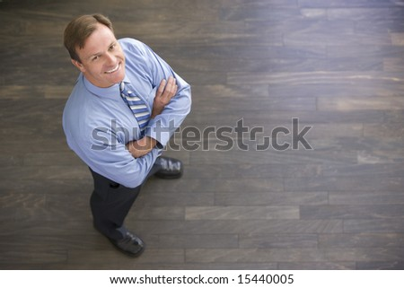 Businessman standing indoors smiling - stock photo