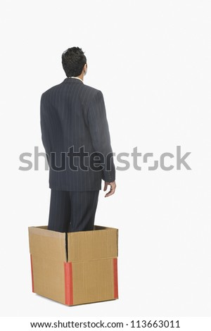 Businessman standing inside a cardboard box