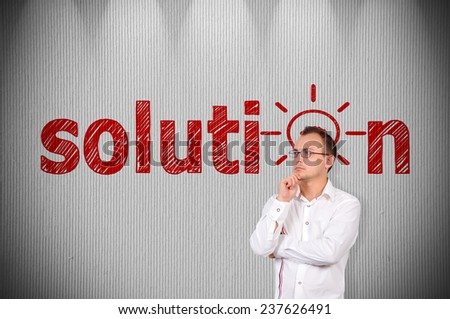 businessman standing near a concrete wall with drawing solution - stock photo