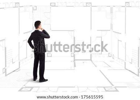 Businessman standing near a house blueprints - stock photo