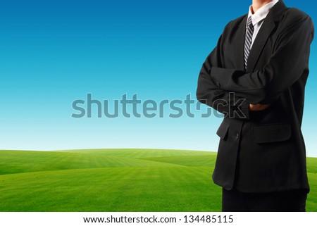 Businessman standing near grass field  blue sky background - stock photo