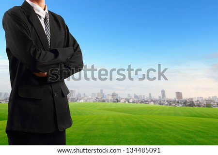 Businessman standing near grass field  blue sky with skyscraper background - stock photo