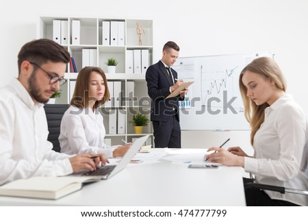 Businessman standing near whiteboard with graphs and taking notes. His colleagues listening to speech.woman sleeping.Man typing.