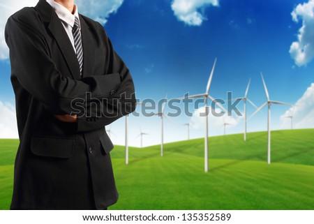 Businessman standing near wind turbine on green grass field - stock photo