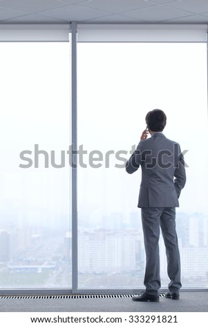 Businessman standing near window, looking at city and talking by phone