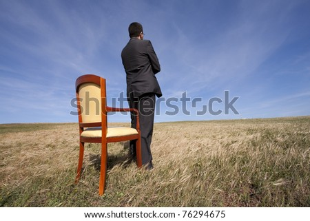 businessman standing next to a chair in outdoor looking to the field