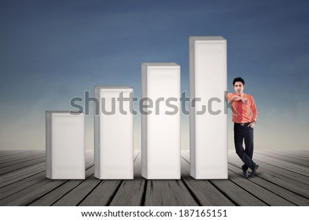 Businessman standing next to bar chart on blue sky background - stock photo