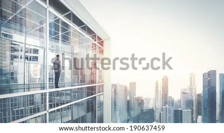 Businessman standing on a balcony and looking at city  - stock photo