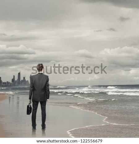 Businessman standing on a beach