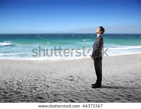 Businessman standing on a beach - stock photo