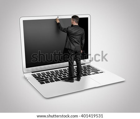 Businessman standing on a big laptop keyboard touches the monitor by his hand