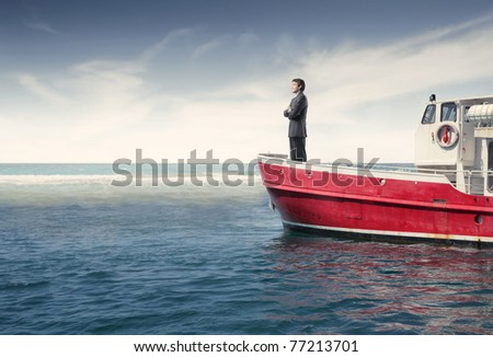 Businessman standing on a boat - stock photo