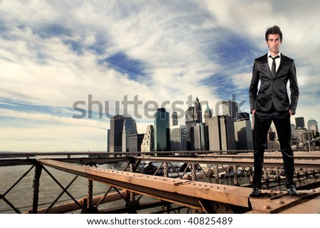 businessman standing on a bridge and manhattan on the background - stock photo