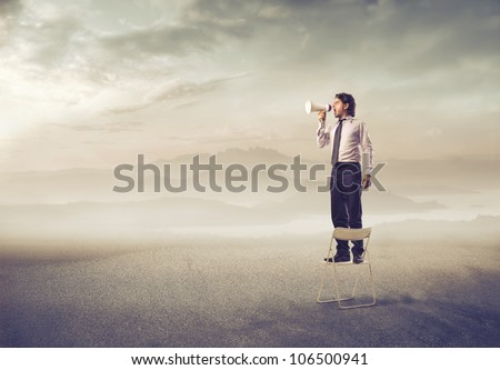 Businessman standing on a chair and screaming into a megaphone in a desert - stock photo