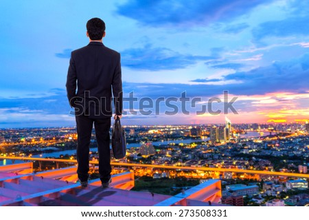 Businessman standing on a city office. - stock photo