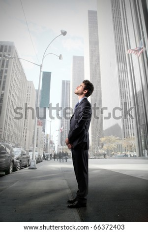 Businessman standing on a city street and looking at the sky