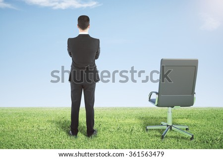 Businessman standing on a green grass and looks away - stock photo