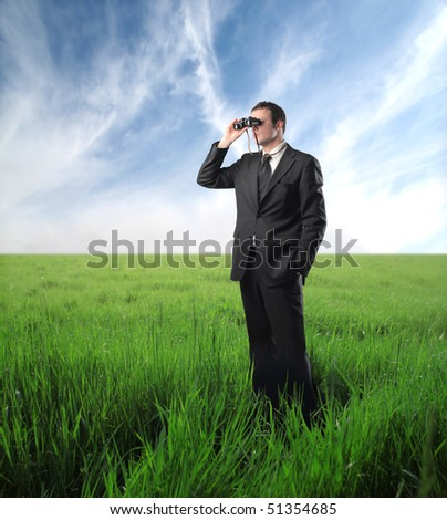 Businessman standing on a green meadow and using binoculars - stock photo