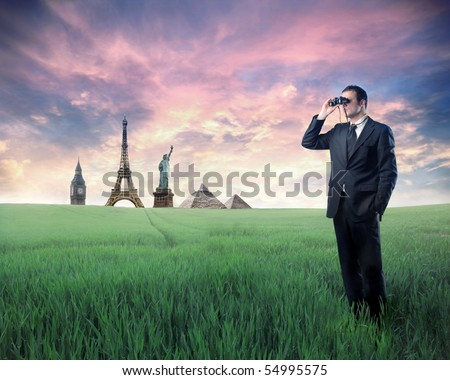 Businessman standing on a green meadow and using binoculars with landmarks from different cities on the background - stock photo