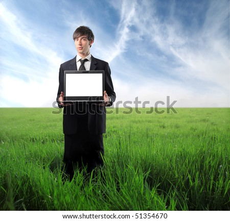 Businessman standing on a green meadow with a laptop in his hands - stock photo