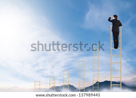 businessman standing on a ladder chart in the sky - stock photo